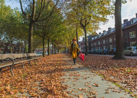 Asian attractive happy trendy senior woman in yellow clothes with red hair walking in autumn alley, perspective view. 写真素材
