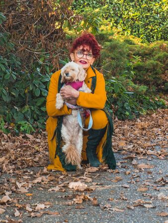 Attractive senior woman walking with her dog in an autumn park.