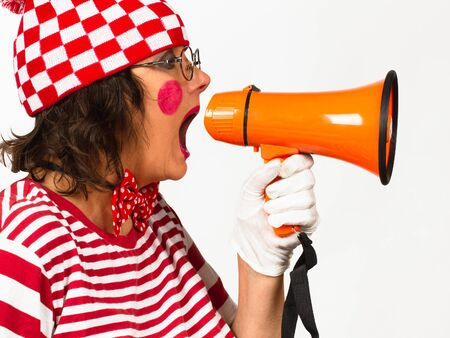 Funny clown in eyeglasses with necktie shouting at the megaphone, view in profile over white background. Stok Fotoğraf