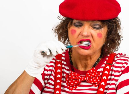 Portrait of a pantomomer with a toothbrush. The clown is wearing red and white clothes, makes funny facial expressions and shows a toothbrush.
