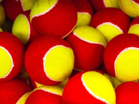 group of yellow and red tennis balls in the sports shop 写真素材