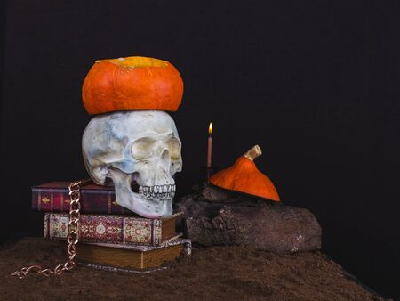 Vintage skull and antique books with necklace, pumpkin  and candle on a dark background with copy space.