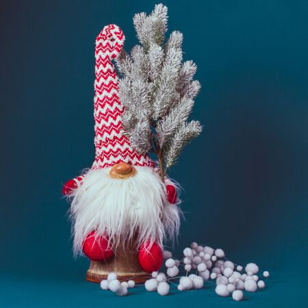 Beautiful decorative gnome with a big boradoi, with a Christmas tree in his hand, dressed in a red and white winter hat, sitting on a blue background