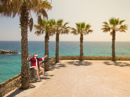 Happy Christmas Relaxation Beach Holiday Concept. Santa Claus sits and laughs with his hands up, relaxing on a sunny day by the ocean