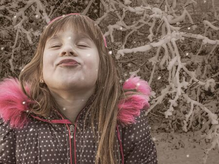 Portrait of joyful cute little girl on a walk in park during a snowfall. Outdated photo effect, retro style. Stok Fotoğraf