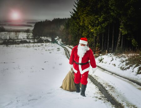 Christmas gifts delivery. Santa Claus, as a courier with a big heavy bag full of gifts, hurries to people, walking along a snowy road along the forest.