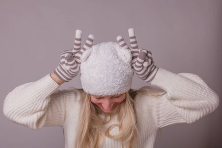 Humorous woman wearing season winter clothes, with long blond hair, makes horns on her head with fingers in knitted striped gloves, pastel colors over gray-lilac background.