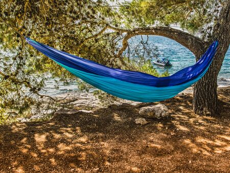 A hammock hanging on a tree high above sea level. Below you can see the sea with a motor boat.