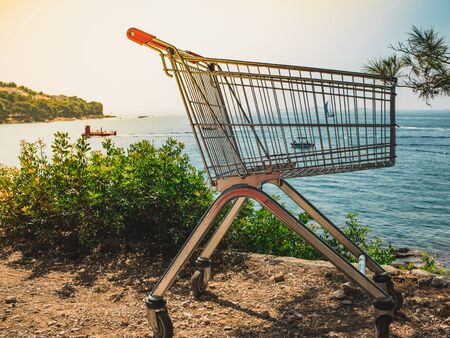 Top view of a beach, sunny day, seacoast, sailboat and closeup of an empty shopping cart. Summer sale concept. Stockfoto - 150296392