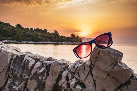Sunglasses lie on a stone against the backdrop of sunset, bays, mountains Stockfoto - 150296394