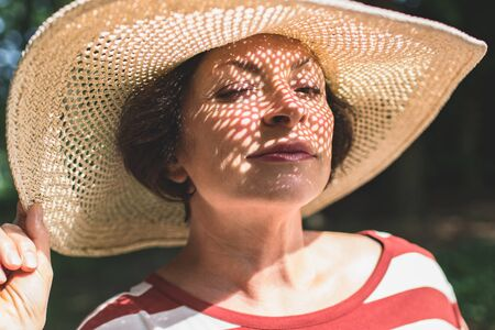 Closeup portrait of mature charming lady in big straw hat with winking eye. Summer vacation, sunny day, outdoor