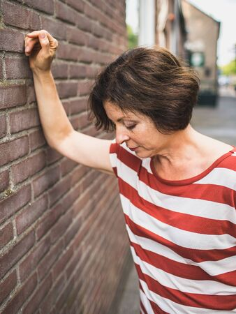 A senior lady in a striped shirt was standing outside and leaning on a brick wall and looking down.