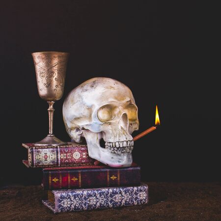 Halloween still life with a skull, antique books, a silver glass of wine and a burning candle on a dark background.