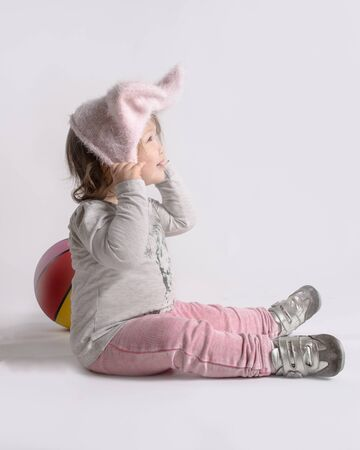 Cute little asian girl baby plays with her hat and bal. Profile, soft colors, space for text.
