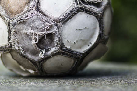 Old damaged soccer ball on a blurred background. Macro photo.