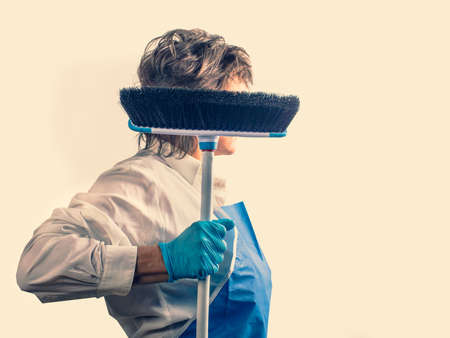 Woman-hero in a blue apron and latex glove with a brush in her hands is ready for thorough work during outbreaks of the influenza virus and the epidemic of coronavirus.