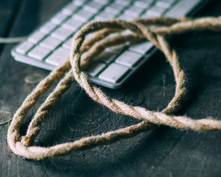 Selective focus on the rough rope, blurred keyboard, dark background.
