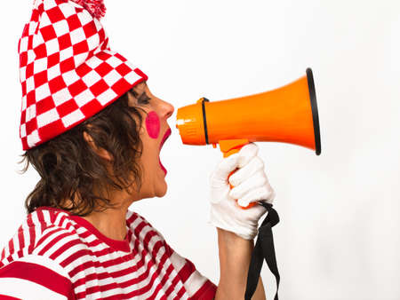 Senior female clown in a checkered hat shouting at an orange megaphone, profile view on a white background with space for your text. 写真素材