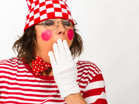 Funny clown in white-red clothing yawns, involuntary open one's mouth wide due to tiredness or boredom. Standard-Bild