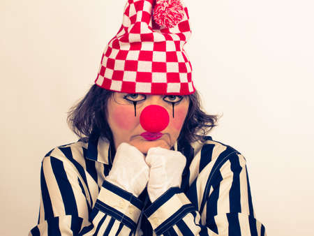Portrait of a sad clown with a red nose and a hat, in a striped blouse on a white background with copy space.