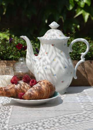 Croissants with ripe fresh raspberries and milk. Spring / summer coffee break outdoor between sunlight and shadow. 版權商用圖片