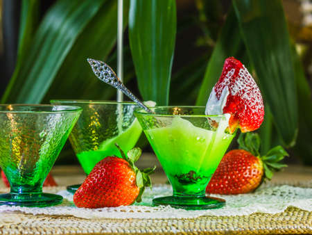 Festive and healthy snack for children. Three green glasses with yogurt and strawberries, vibrant colors. Zdjęcie Seryjne