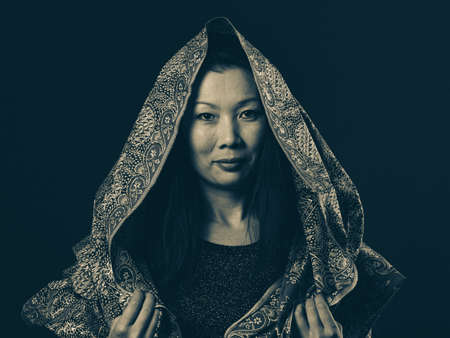 Mysterious riddle, portrait of a elegant Asian woman covered with patterned shawl, old-style photo.