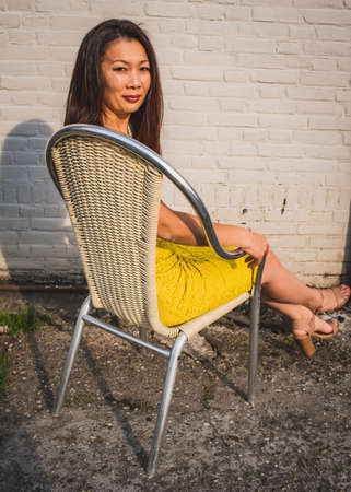 Asian model of average age in a yellow dress sits against the background of a white brick wall, outdoor, Industrial space.