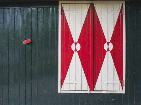 Traditional Dutch closed window with shutters, simple graphical patterns in red, green, white.