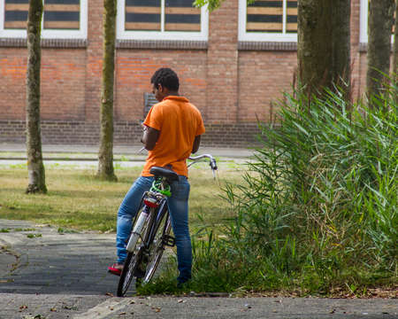 Young black man resting on his bicycle and using his phone, view from back outdoor