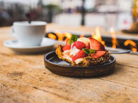 Close-up elicious pastry with fresh strawberries and a cup of coffee on the rough wooden background of table with fire. Outdoor terrace of restaurant in centrum of Zierikzee, Netherlands.