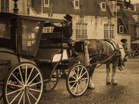 Old Amsterdam, Dam Square - the historical center of Amsterdam. Image of horses with carriage and coachman in antique style.