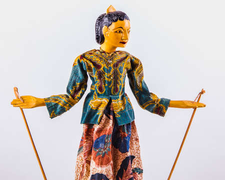 Indonesian woman traditional puppet in folklore clothes on a white background, copy space for your object or text.