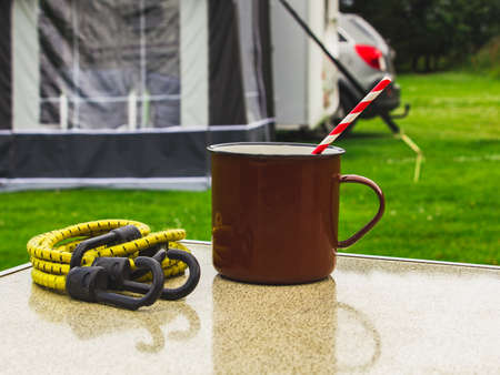 Close-up photo of brown metal mug with drinking straw on the table in camping. Travel by car, mobile life.