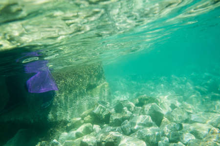 Turquoise water with stones, concrete, a purple mesh at the bottom of the sea. Stok Fotoğraf
