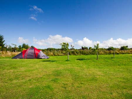 Tourist tent in a camp among meadow Zdjęcie Seryjne
