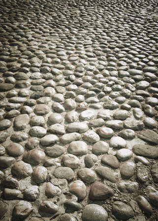 Street with polished stones in Balkan, background with texture.