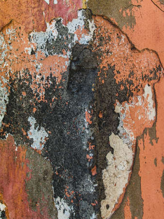 Grungy concrete wall background texture with damaged layers of stucco and pink paint, frontal photo, close-up. Фото со стока