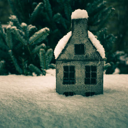 Winter snowy background with a cozy decorative house. Dark green tone with blur.