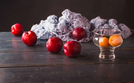 Beautiful still life with apricots, red plums, knitted blue wool on a rustic table and dark background and light effect.
