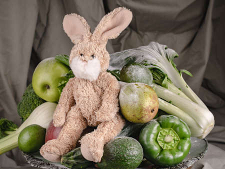 A toy rabbit set against a background of green vegetables and fruits such as broccoli, apple, lime, pear, bok choy, fennel, salad and others.
