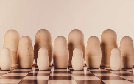 Group of blank russian nesting dolls. Unpainted wooden nesting dolls on a chessboard.No face detected.