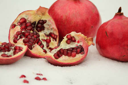 Whole and broken ripe fruit pomegranates on the snow on a winter day. Still life of pomegranates in the snow.