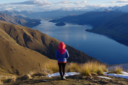 Lady hiker standing on top of the mountain - isthmus peak with a view of the Wanaka Lake Stock Photo