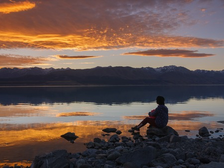 dreamer, silhouette of woman sitting along the lake at sunset, human strength, psychology concept Stock Photo