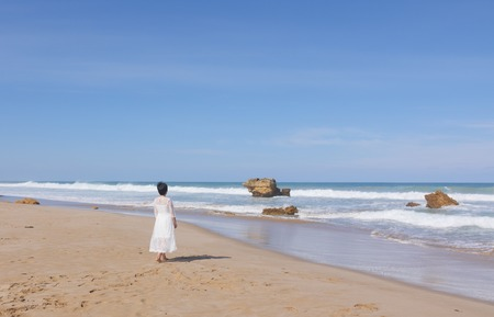 Girl in wedding dress running along the beach Stock Photo