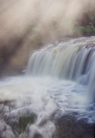 beautiful waterfall in rays of sunshine