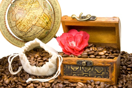 a treasure chest filled with coffee beans placed side by side with a globe, a red camellia flower and a bag of coffee beans photo