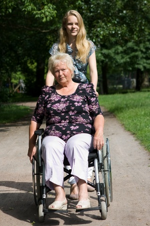 Senior woman in a wheelchair and her granddaughter photo