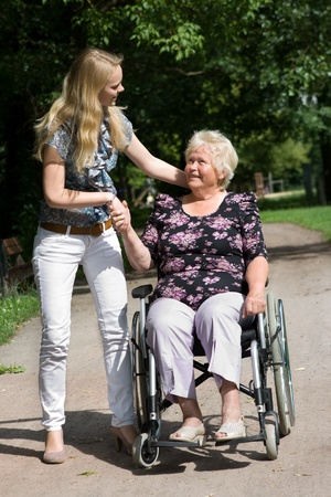 Senior woman in a wheelchair and her granddaugther Stock Photo